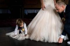 Zoontje helpt met de trouwjurk